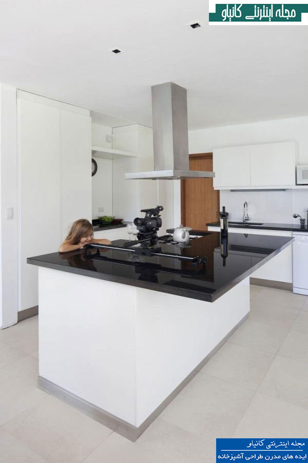 آشپزخانه بسیار ساده و مطبوع دارای یک جزیره سفید با یک صفحه سیاه